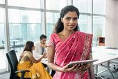 Confident Indian business woman looking at camera while holding a tablet in a modern meeting room poster