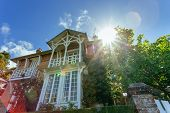 Country House With Green Fence In The Region Of Normandy, France On A Sunny Day With Sunbeams In Blu poster