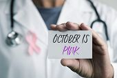 closeup of a young caucasian doctor man with a pink ribbon for the breast cancer awareness pinned in poster