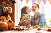 Mother and her daughter having fun at home. Happy Family preparing for Halloween. Mum and child cook poster