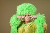 foto of drag-queen  - Flamboyant drag queen in boa hat on green background - JPG