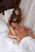 image of seminude  - young Caucasian heterosexual couple resting in bed - JPG