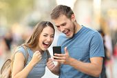Excited Couple Receiving Good News On Line Outside poster