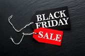 Black Friday Sale tags on dark background poster