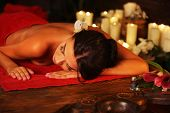 Massage of woman in spa salon. Girl on candles background in massage spa salon. Luxary interior in o poster