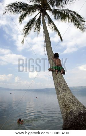 SUMATERA - FEBRUARY 10: Village children frolic and play in Lake Singkarak, a tectonic lake in Sumatera, Indonesia on Feb 10, 2012. It is the biggest lake in Sumatera measuring 20km long and 8km wide.