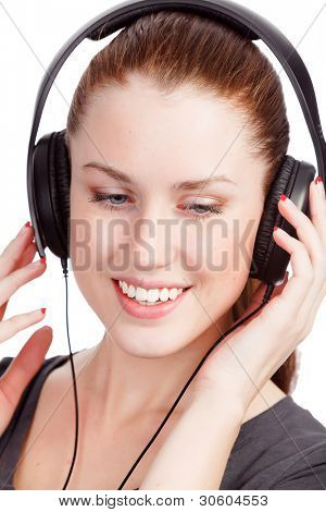 Pretty girl listening music and smiling to you. Isolated on white background