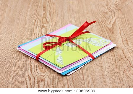 Bunch of color envelopes with ribbon on wooden background