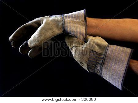 Homem de calçar as luvas de trabalho
