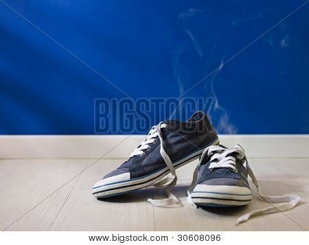 Stinking Worn-out Shoes Left On Wooden Floor