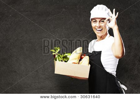 portrait of middle aged woman carrying food against a vintage wall