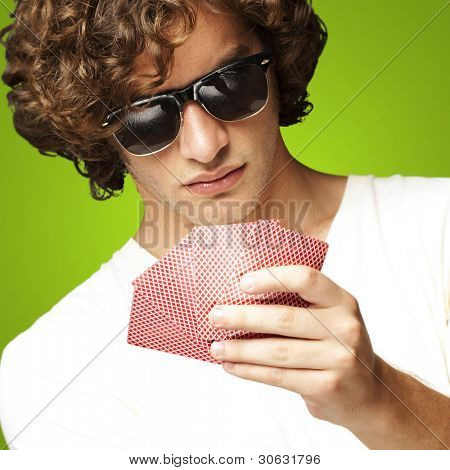 portrait of young man wearing sunglasses and playing poker over
