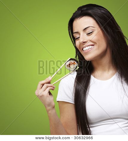 young woman eating a sushi piece against a green background
