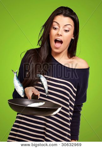 portrait of young girl cooking unruly fishes on pan over green background