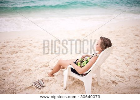Pensive thinking woman sitting on the beach