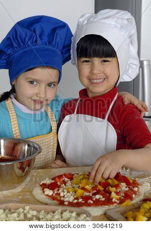 Two Little girls cooking pizza in a kitchen.Little kid in a kitchen together.