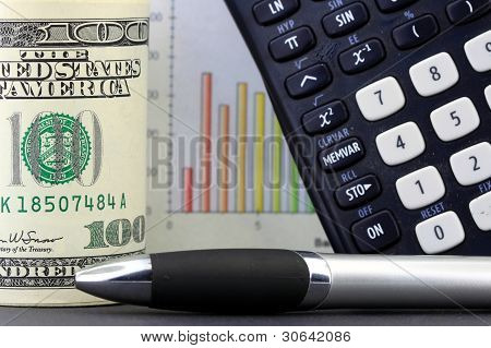 Sales charts, calculator and one hundred dollar bills in a roll.