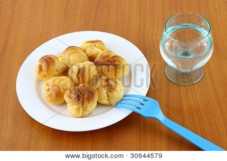 Eclairs on plate on wooden table