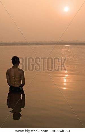 Hindu pilgrim take a bath in the ganges river in Varanasi, India.