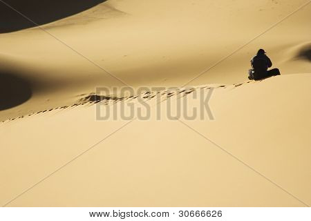 Silhouette of a person seat alone in the dune desert, Morocco