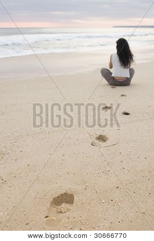Tranquility meditation scene. Young female doing yoga on a quiet yellow sand beach