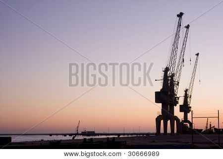 Group of huge sky cranes at a construction site at sunset, silhouette against orange sky