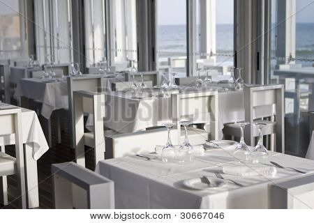 tables and chairs in stylish restaurant on an ocean coast, with sea view - Algarve, south of portugal