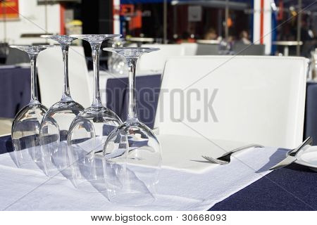 Table setting at a European michelin restaurant (Glasses of wine set on white dining table)