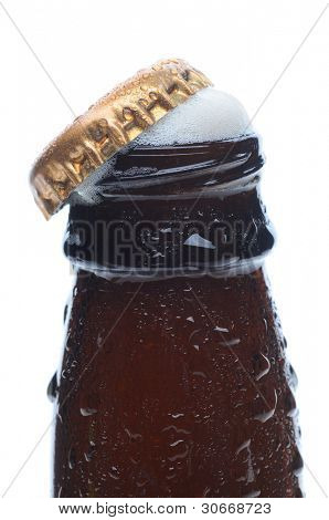 Closeup of a beer bottle top with the cap askew and foam bubbling up. Vertical format over a white background.