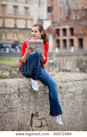 Pretty young female tourist studying a map at the Trajan's forum in Rome, Italy (dome of the Santissimo Nome di Maria church in the background)