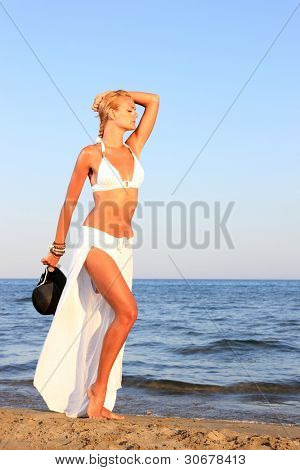 young woman showing her fit body in bikini at beach