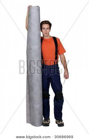 Tradesman holding a roll of linoleum flooring