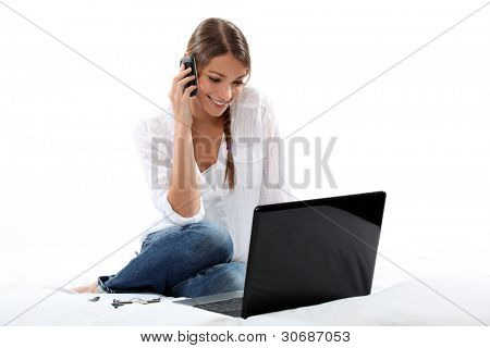 Woman talking on the phone and looking at her laptop