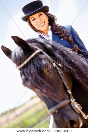 Beautiful horsewoman riding a horse outdoors and smiling