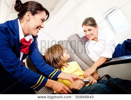 Air hostess helping a kid to fasten his seatbelt