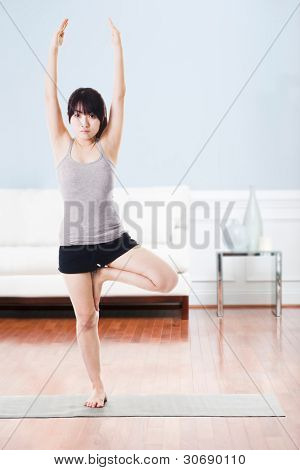 Asian woman on a yoga mat doing the tree pose.