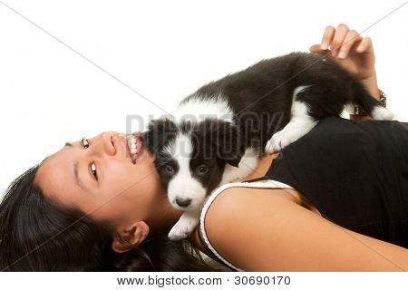 Young woman playing with a 5 weeks old border collie puppy