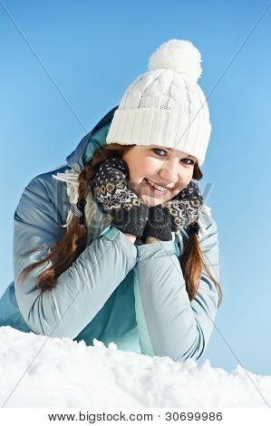Portrait of happy young smiling woman in warm clothing outwear at winter snow outdoors over blue sky