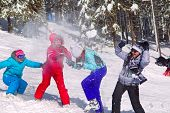 foto of snowball-fight  - Girls having snowball fight in snow in winter background - JPG