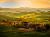 Amazing colorful sunset in Tuscany. Picturesque agrotourism and typical curved road with cypress, Cr poster