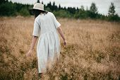 Stylish Girl In Linen Dress And Hat Walking Among Herbs And Wildflowers In Field. Boho Woman Relaxin poster