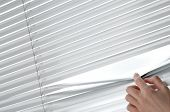 Female Hand Opening Venetian Blinds With A Finger