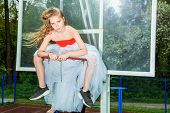 A full length portrait of a sporty teenager girl posing on the basketball pinch in a white fluffy sk poster