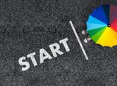 Start. Top View Of A Man With Colorful Rainbow Umbrella Next To Start Line And Start On Asphalt poster