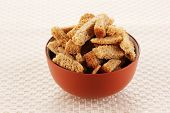 Appetizing rusks in bowl on beige napkin