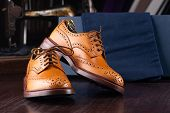 Brown full grain leather brogues on wooden display in in men shoes boutique store with box and cloth poster