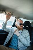 Cheerful Optimistic Taxi Passenger In Sunglasses Holding Handle Inside Of Car And Drinking Coffee Wh poster