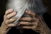 picture of elderly woman  - elderly woman holding head in her hands with severe depression - JPG