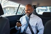 Successful african businessman working on phone witting in car. Mature smiling business man in forma poster