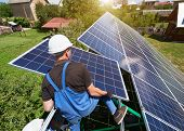 Standing On High Metallic Ladder, Worker Keeping Solar Panel. Installing Solar Batteries Screen On H poster